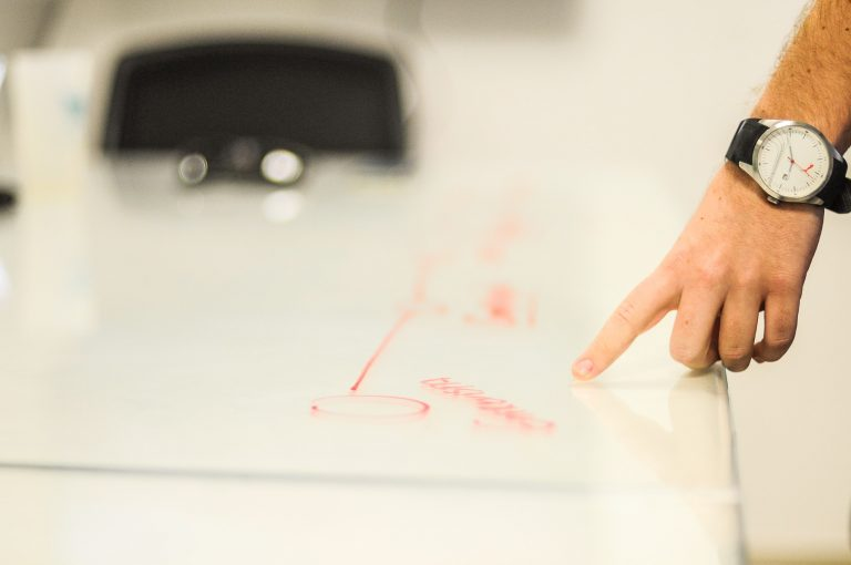 propertystream employee pointing to a diagram on a white piece of paper which is a plan for a new website